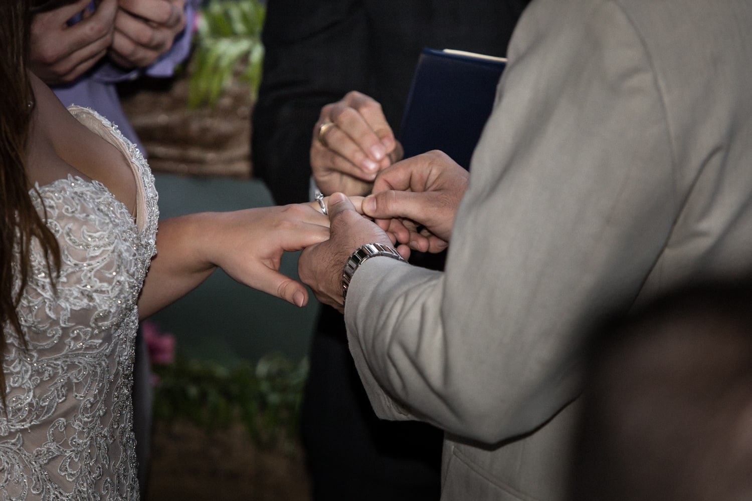 Bride and groom exchange wedding rings after saying vows.