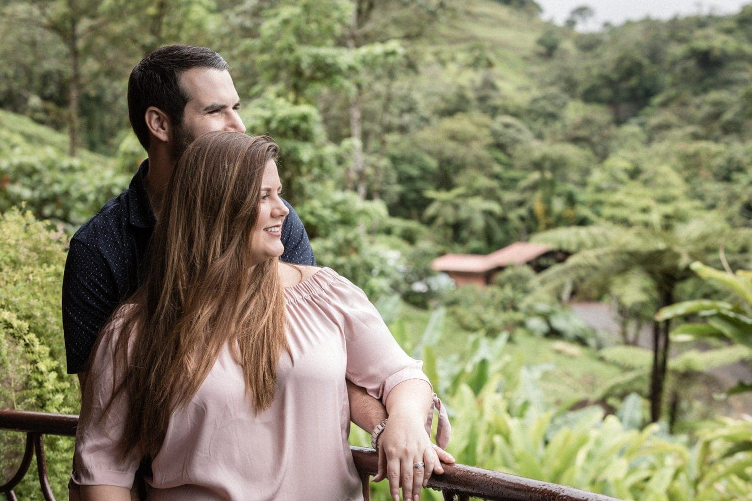 Engaged couple looks at cloud forest from balcony at La Paz Waterfall Gardens.