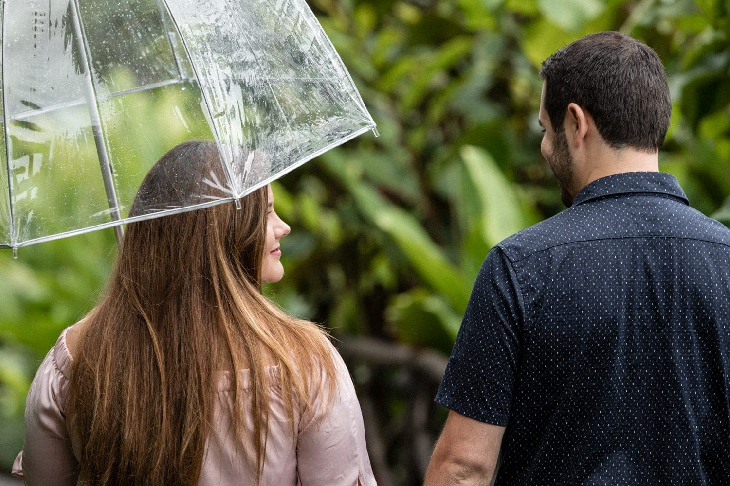Fiancée holding umbrella looks at her love while walking in cloud forest.