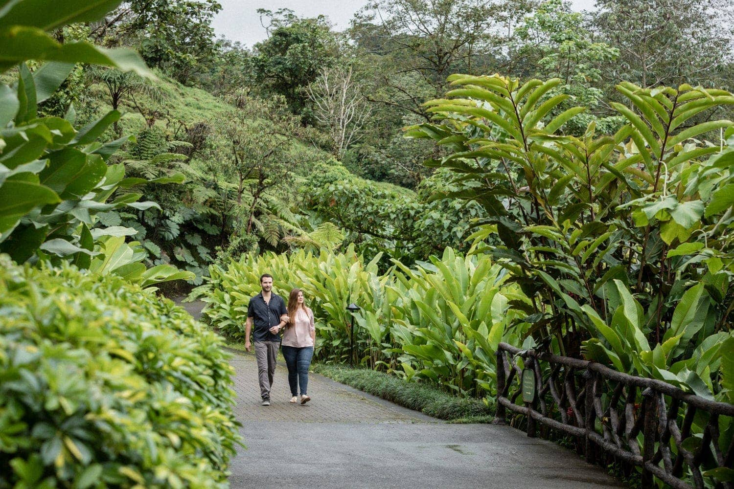 Couple holding hands and walking on path La Paz Waterfall Gardens.