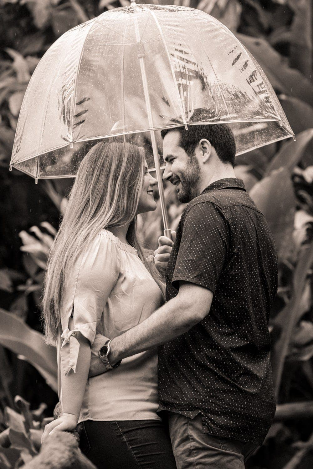 Lovers share an intimate moment under umbrellas during Costa Rica engagement session.