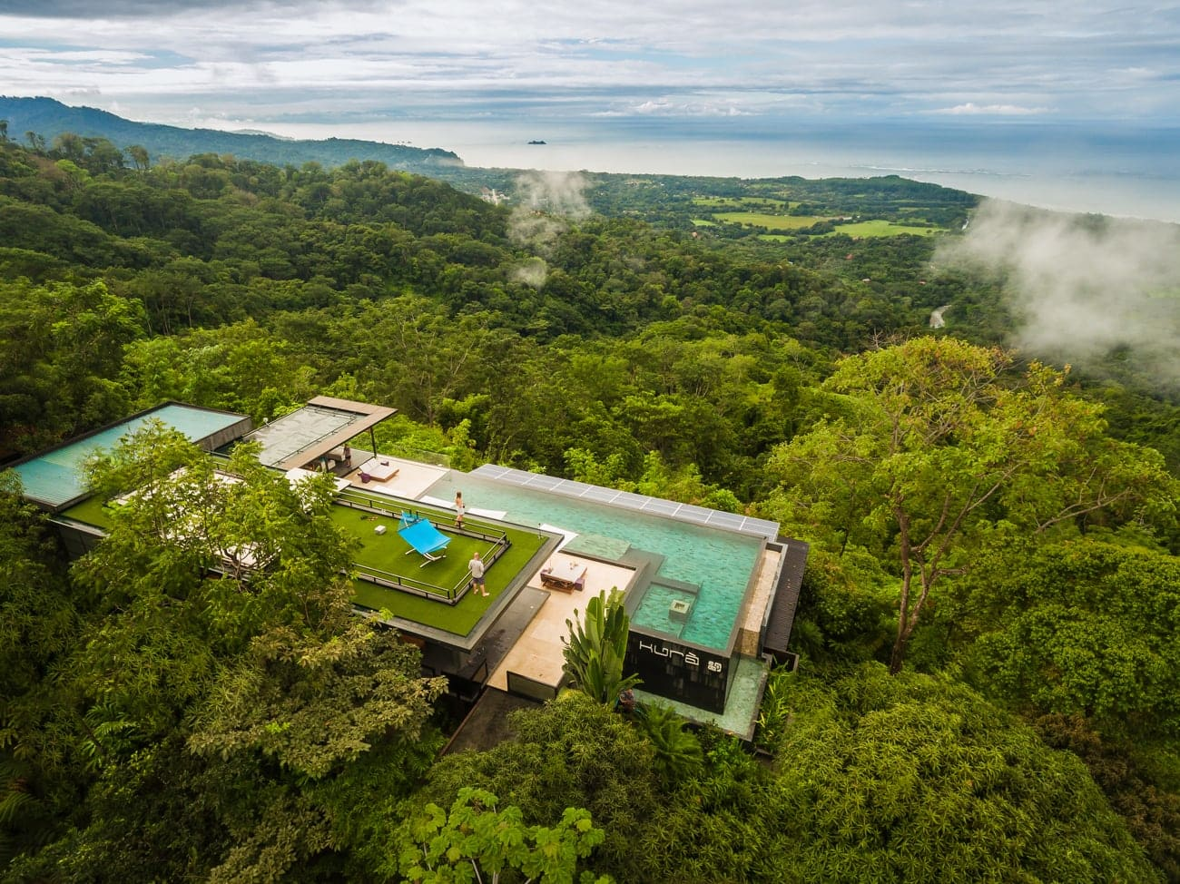 Arial view of Kura on hilltop in rainforest in Costa Rica with Pacific Ocean in the background.
