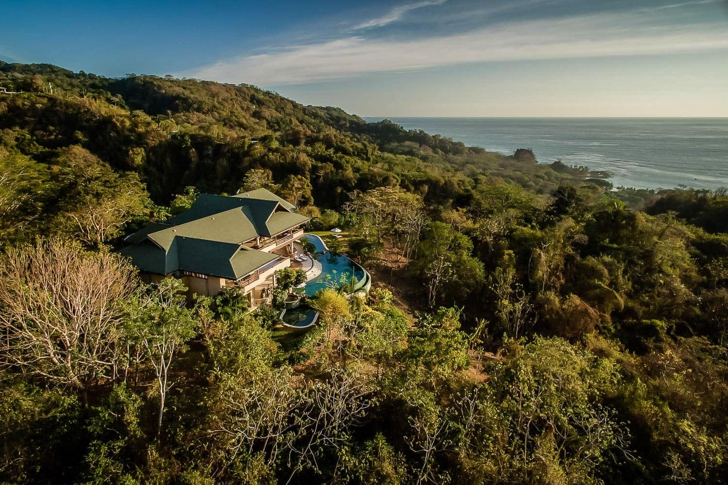 Arial view of Villa Nimbu nestled in rainforest with the Pacific Ocean in the background.