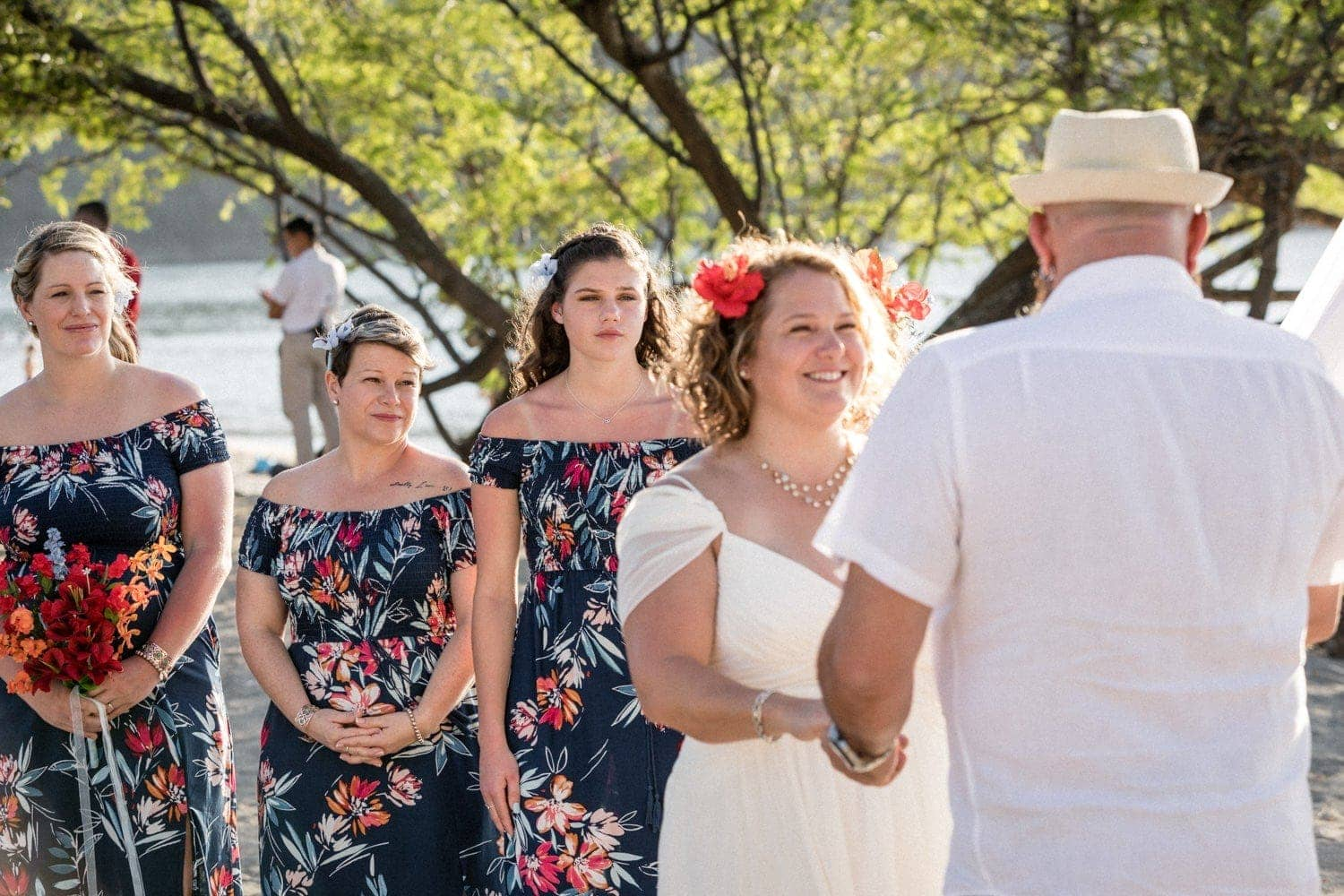 Bridesmaids watch as couple gets married on the beach in Costa Rica.