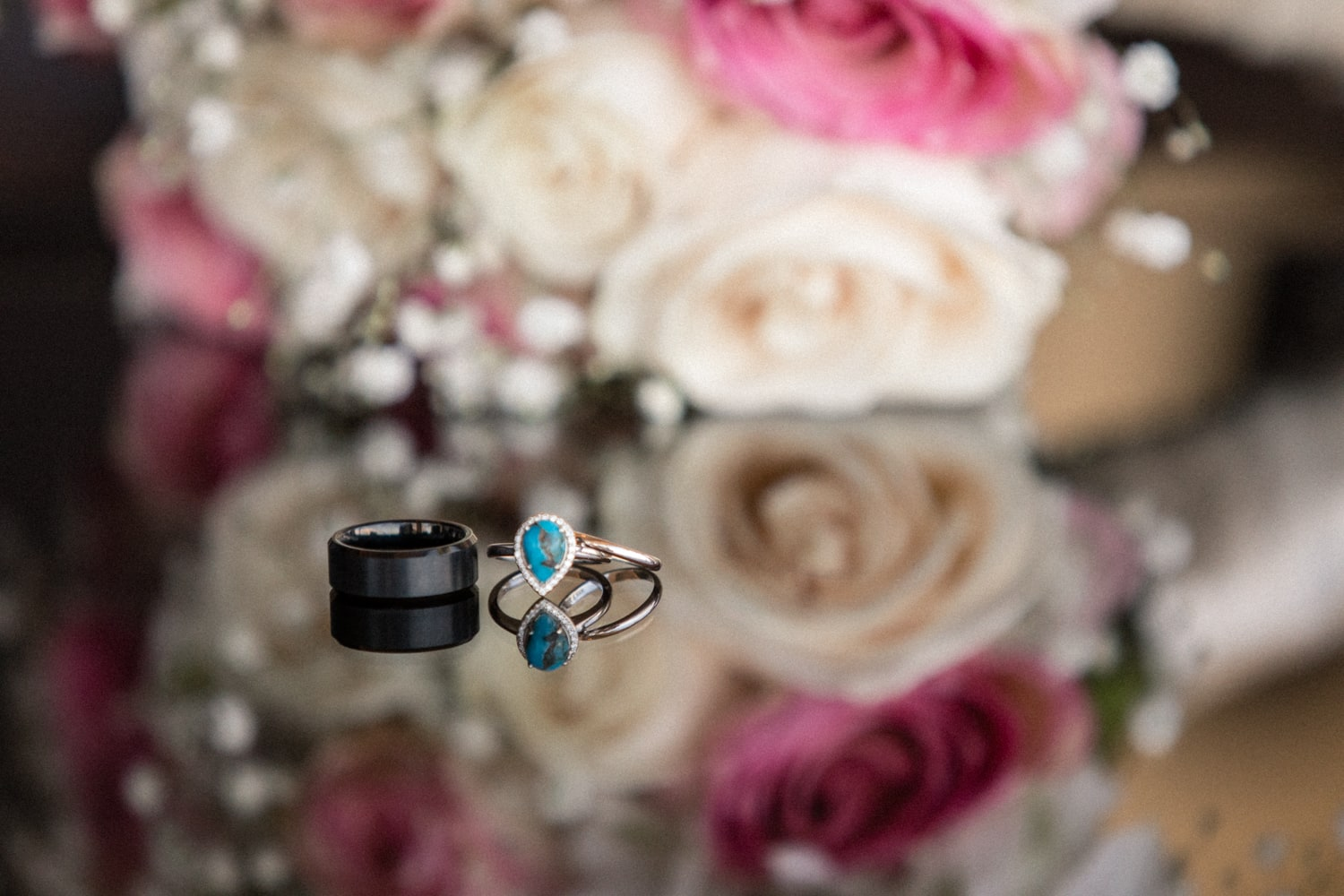 Wedding rings on glass table in front of bridal bouquet.