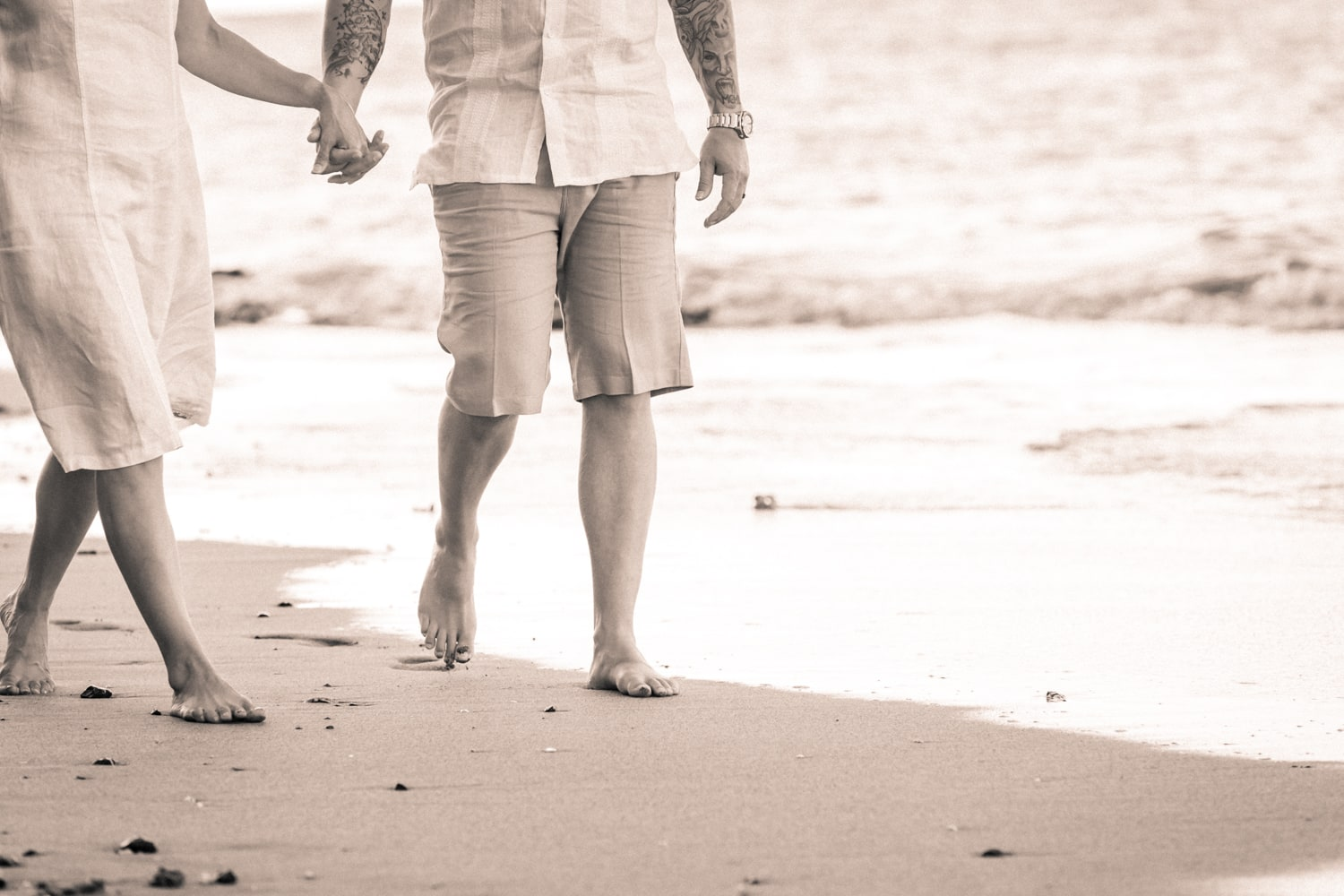 Just married couple walking on beach holding hands.
