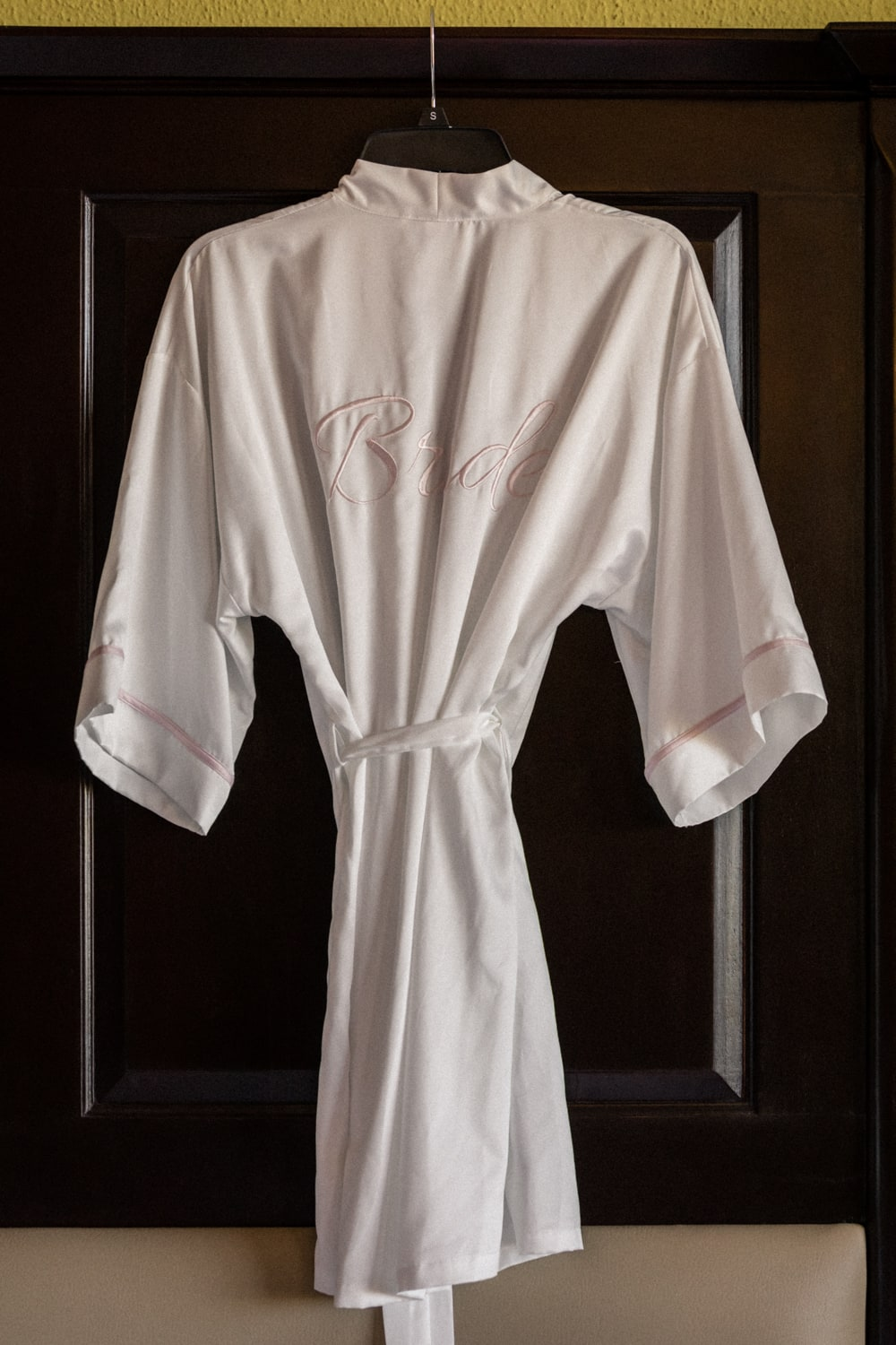 White robe fro bride hanging on headboard in bridal suite.