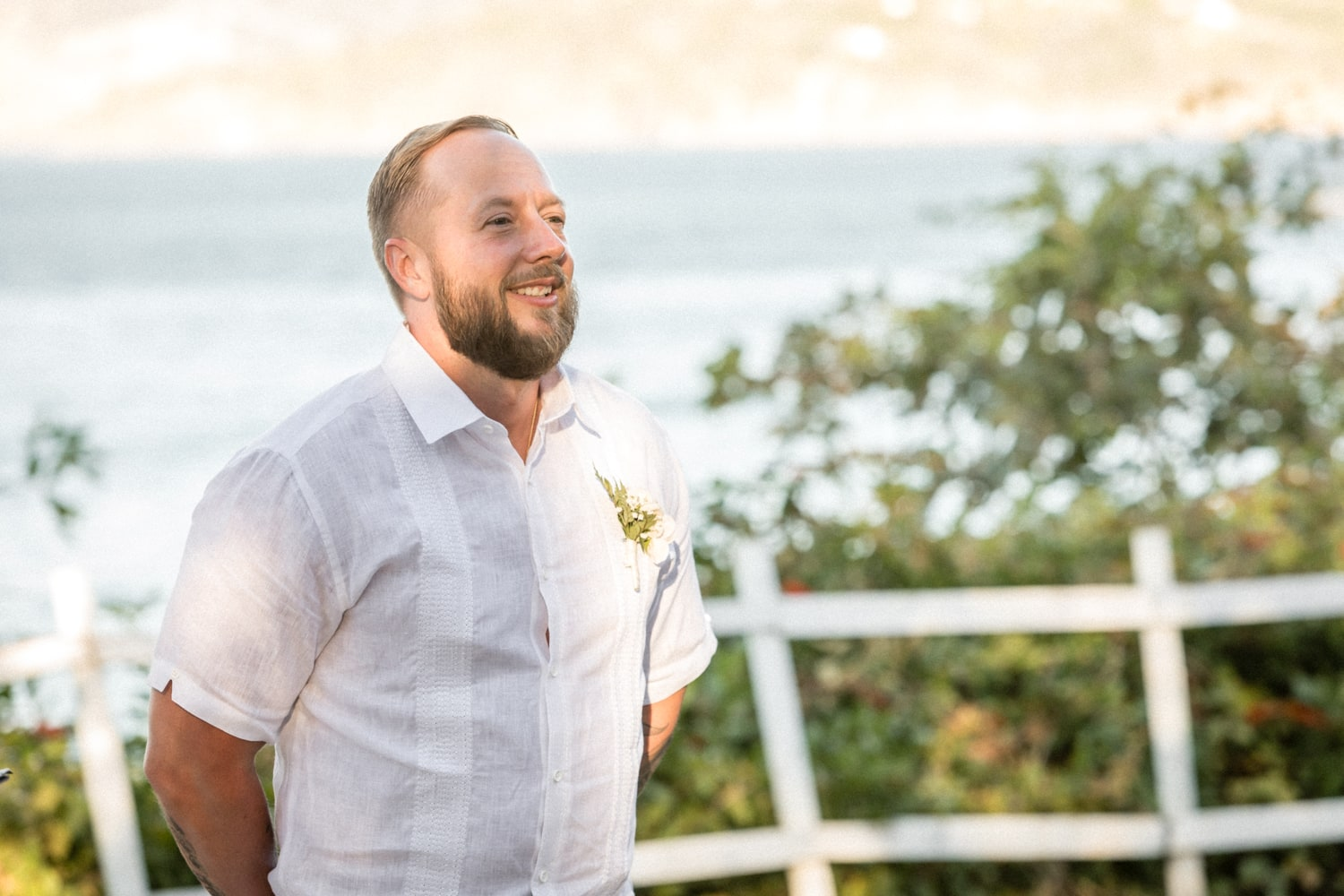 Groom waits for bride at altar with amazing ocean views.