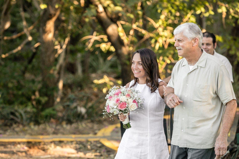 Father escort bride in white wedding dress to altar.