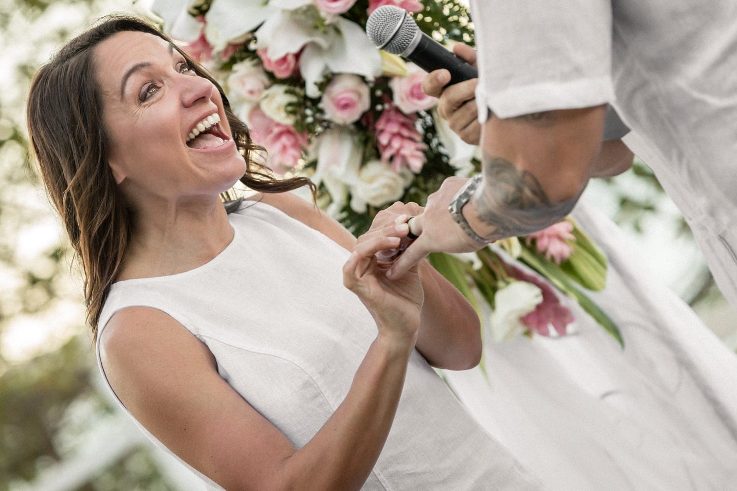 Bride smiles as she and the groom exchange wedding rings.