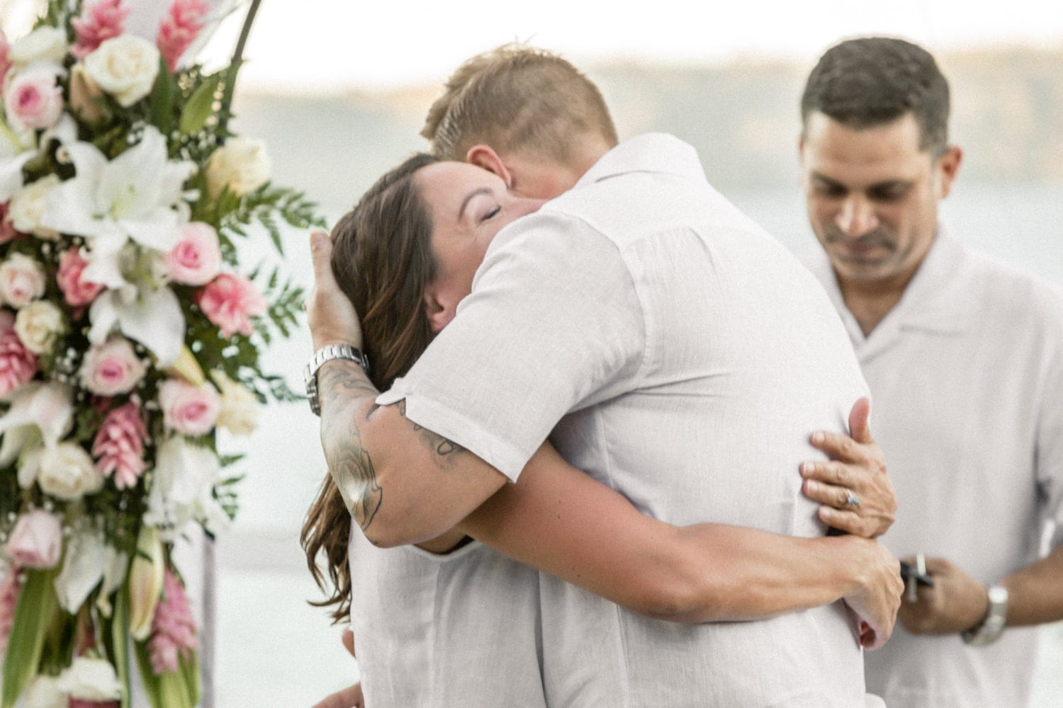 Couple hug after exchanging vows and wedding rings.