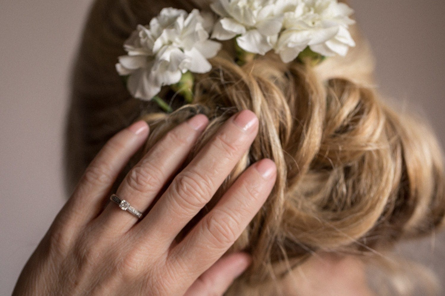 Bride with white flowers in hair during bridal preparation.