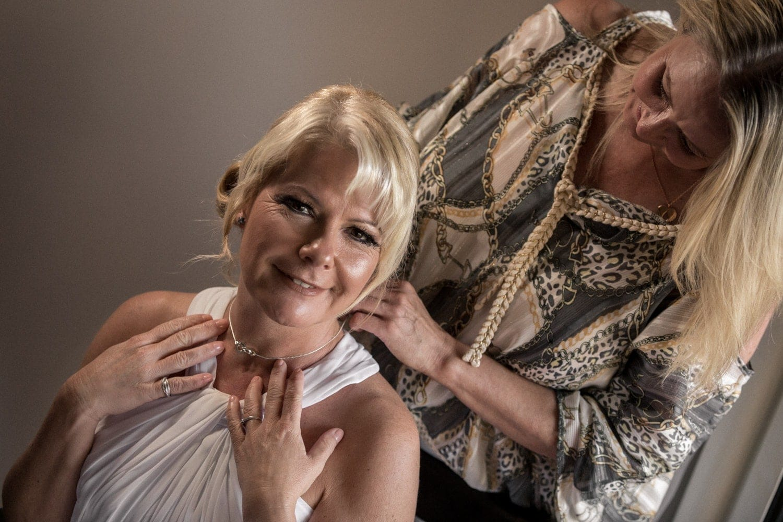Bridesmaid helps bride put on wedding-day jewelry.