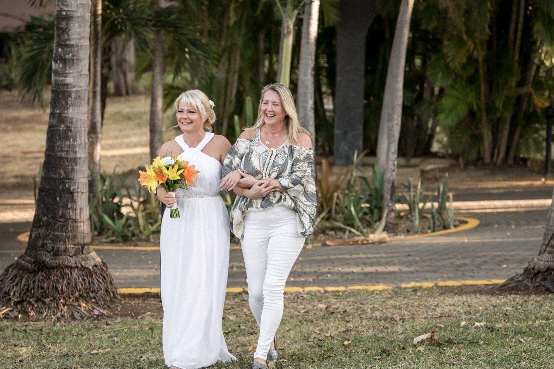 Bridesmaid walks bride to altar at tropical wedding ceremony location.