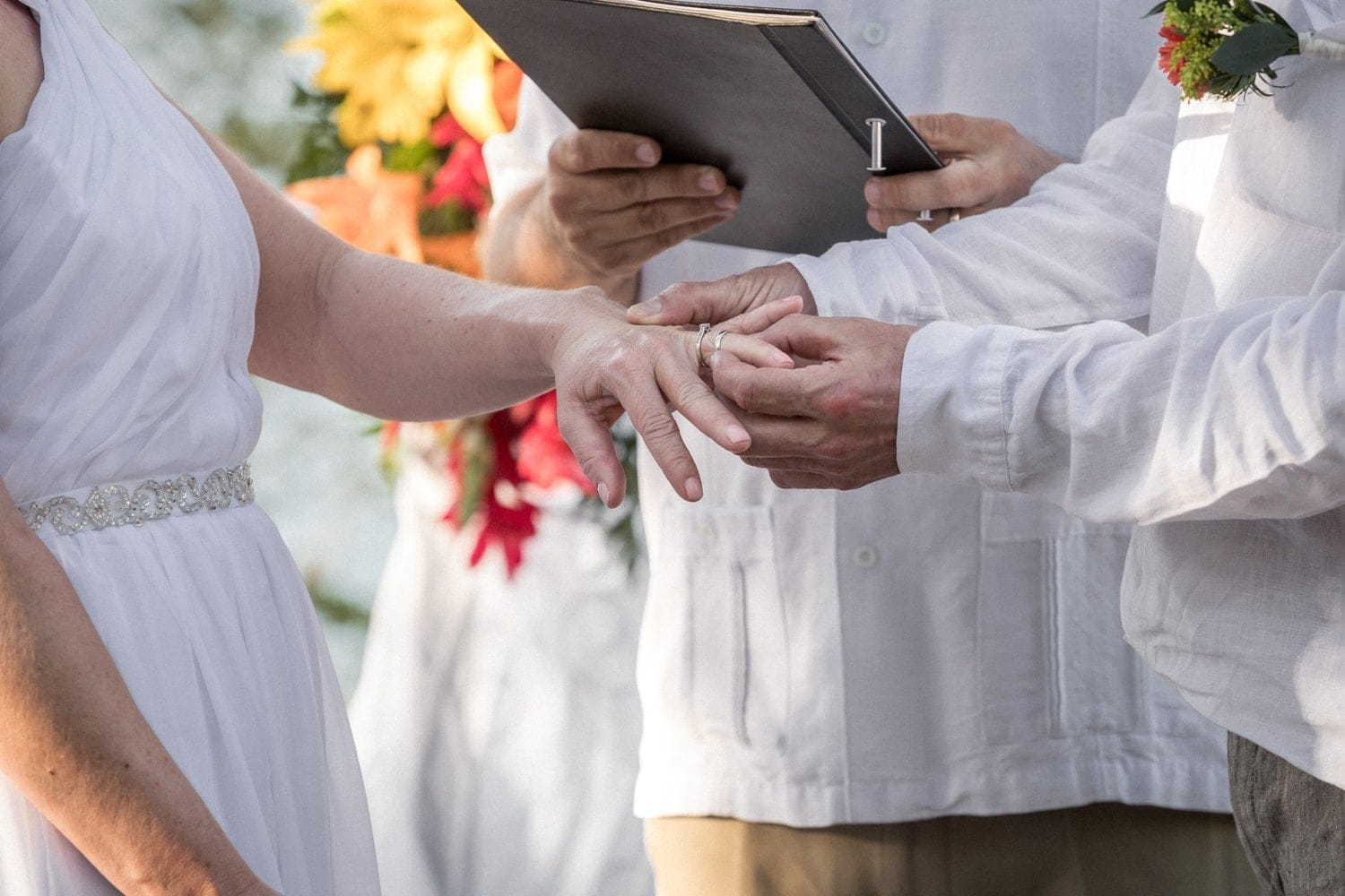 Groom puts ring on bride's finger during wedding ceremony at Occidental Papagayo Resort.