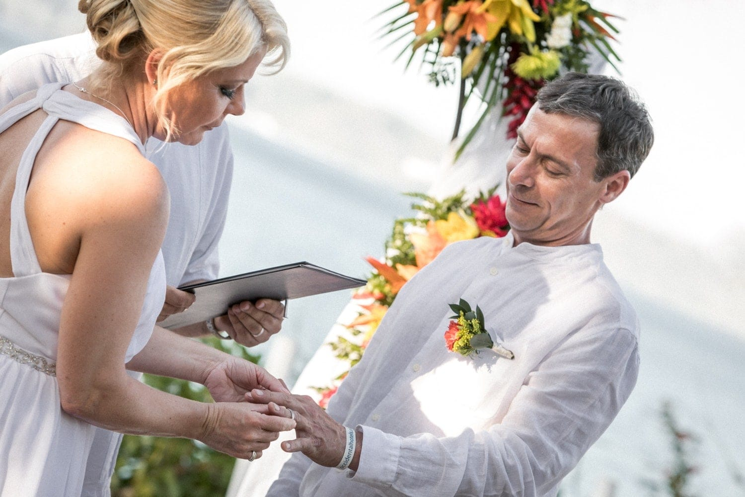 Couple exchanging rings during wedding ceremony with beach in background.