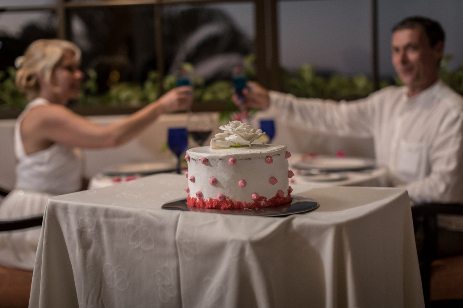 Wedding day cake with bride and groom in background at table toasting.