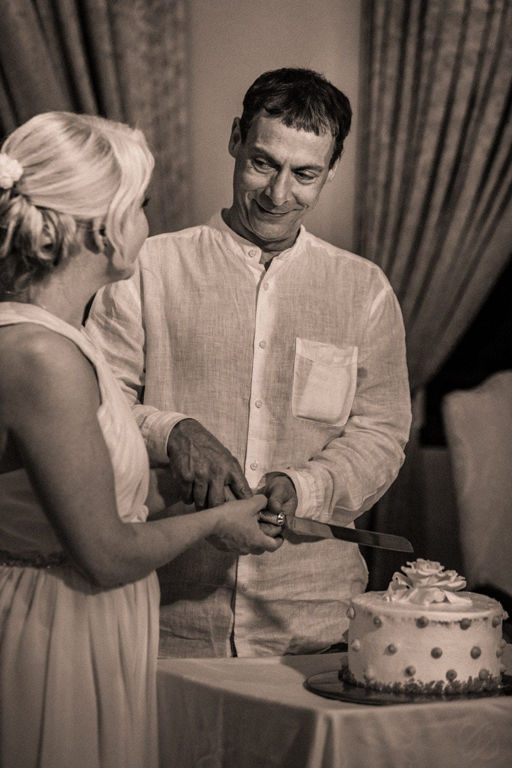 Just married couple cut their cake during wedding reception in Costa Rica.