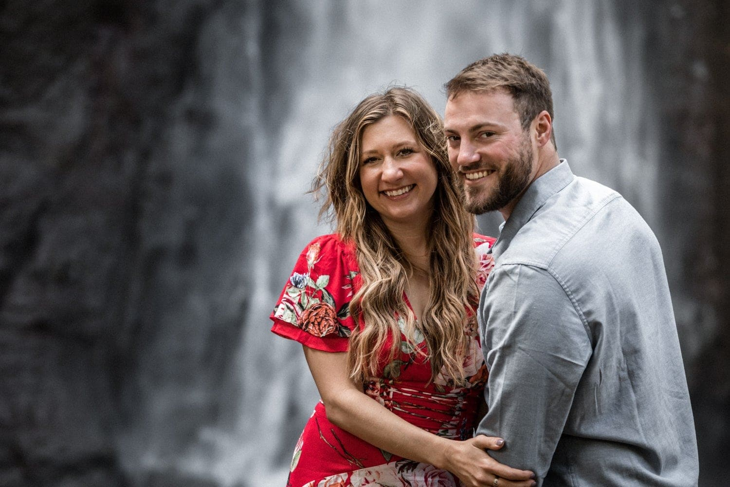 Couple in front of waterfall looks at camera after getting engaged.