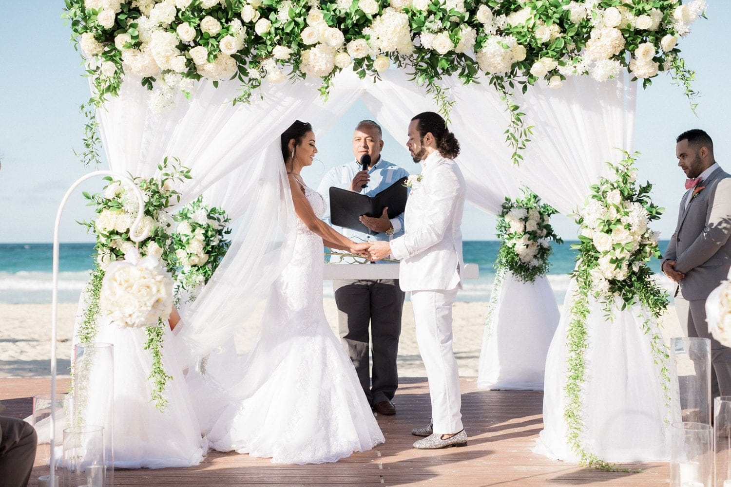 Bride and groom holding hands at altar on gorgeous Punta Cana beach.