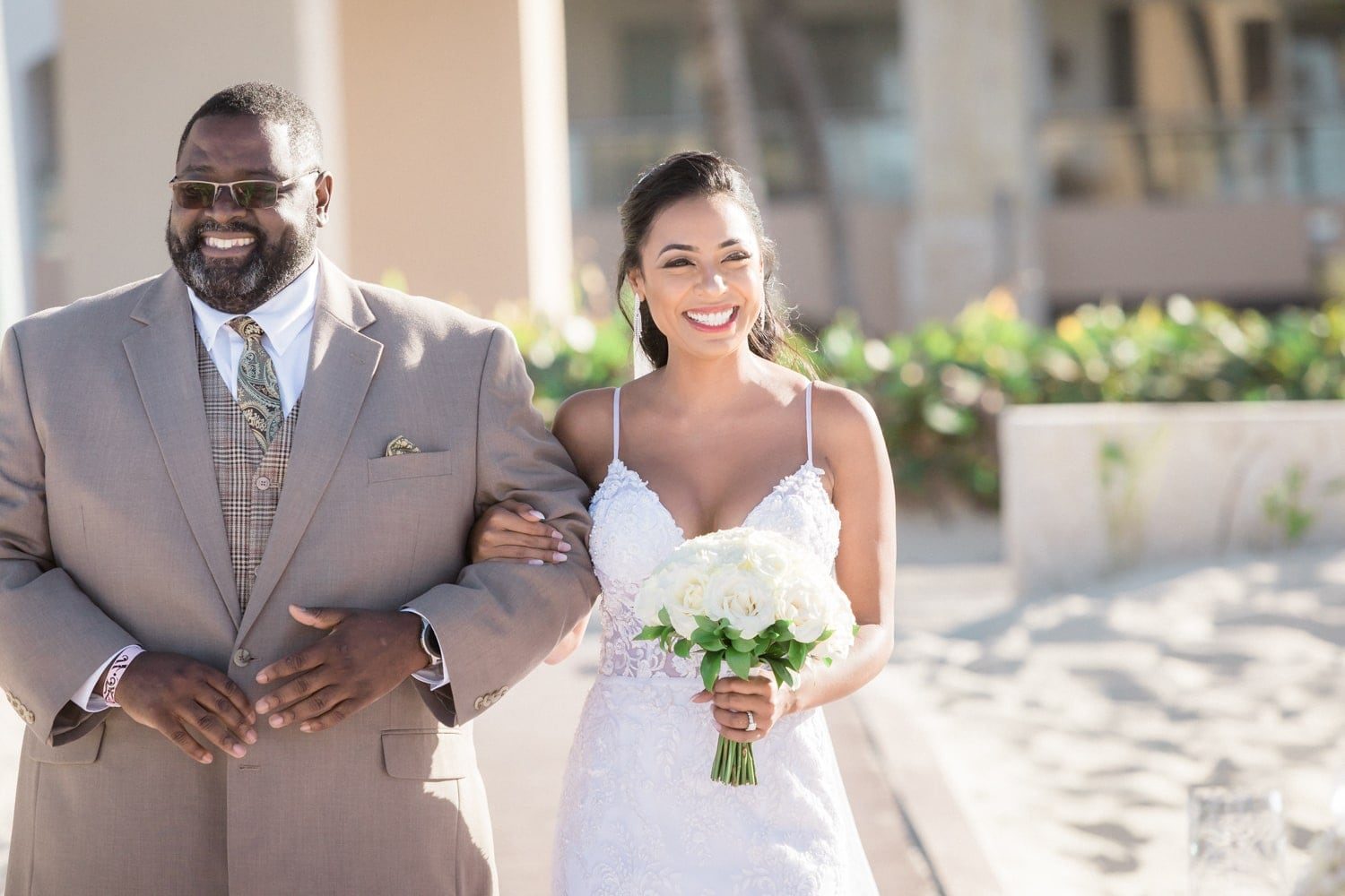 Bride smiles as father walks her to the altar at Hard Rock Resort, Punta Cana.