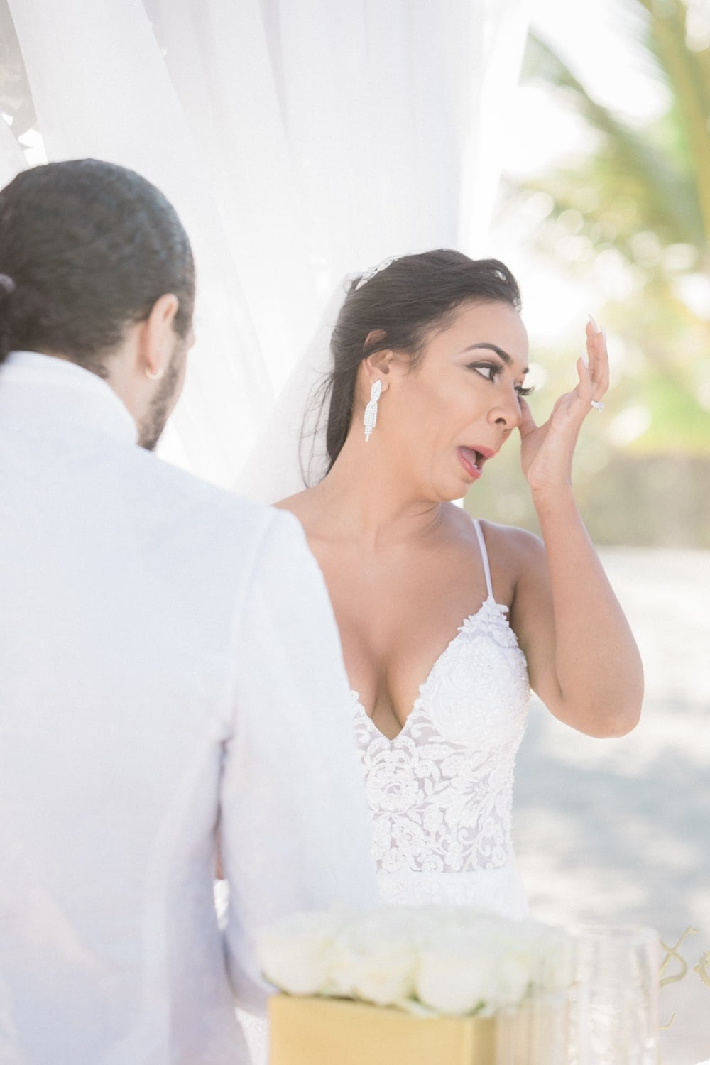 Bride wipes away tears as fiancé says his vows during beach wedding in Punta Cana.