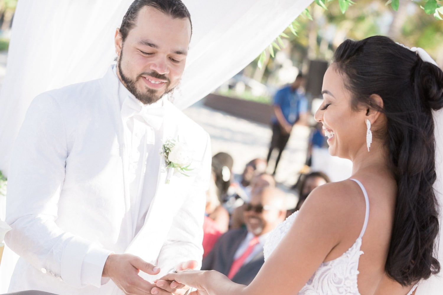 Photo of bride and groom exchanging rings during beach wedding ceremony.