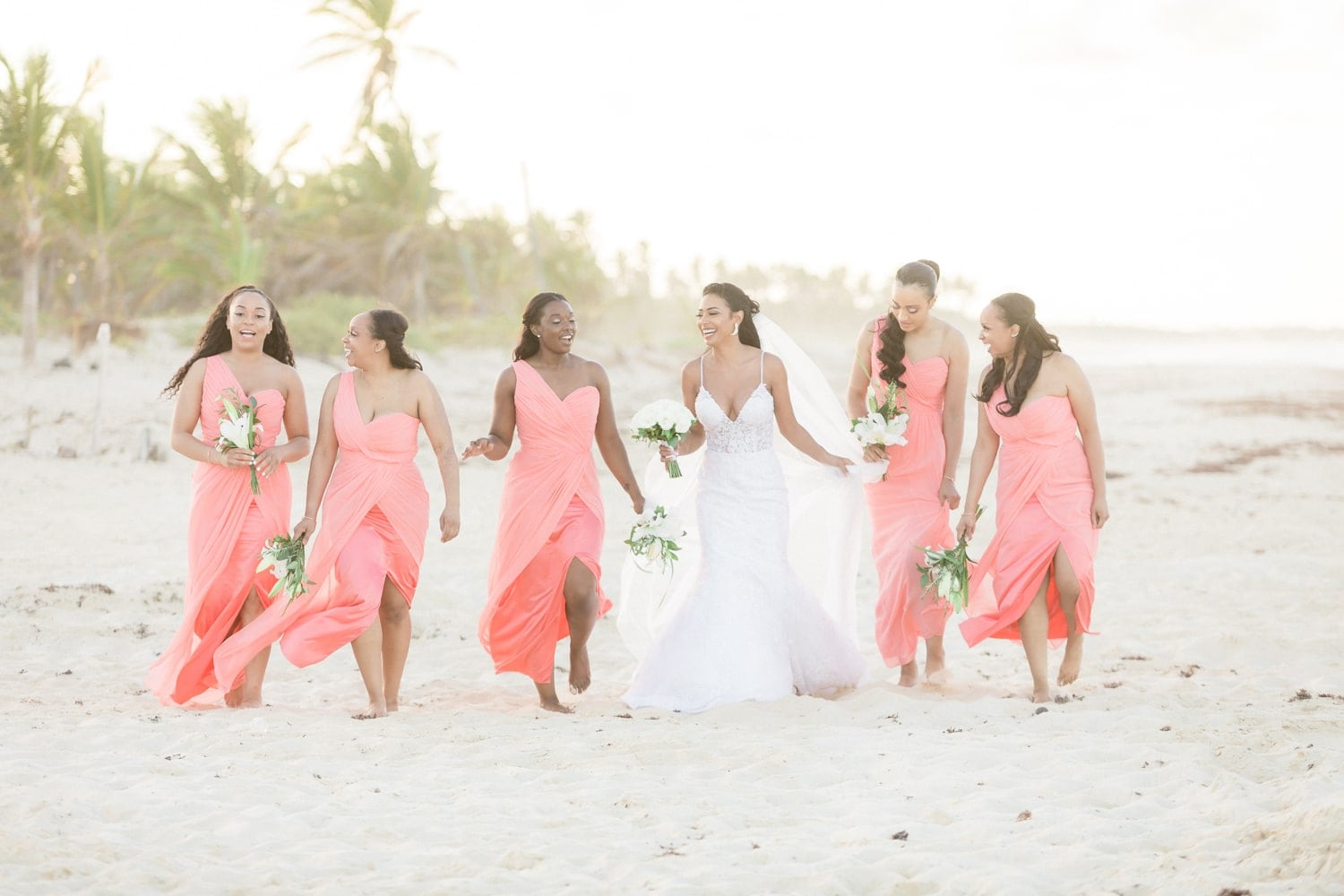 Bride and bridesmaids walking on beach at Hard Rock in Dominican Republic.