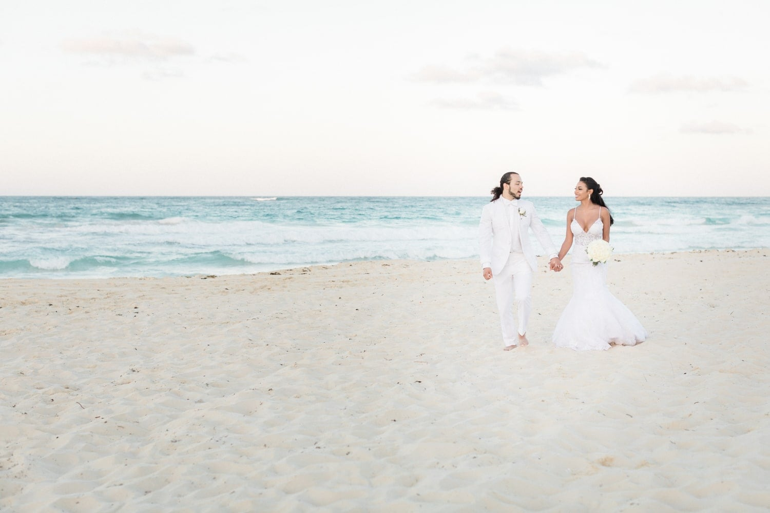 Just married couple walking on amazing beach at Hard Rock Resort in Punta Cana.