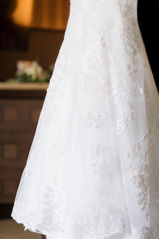Photo of beautiful wedding dress hanging in bridal suite.