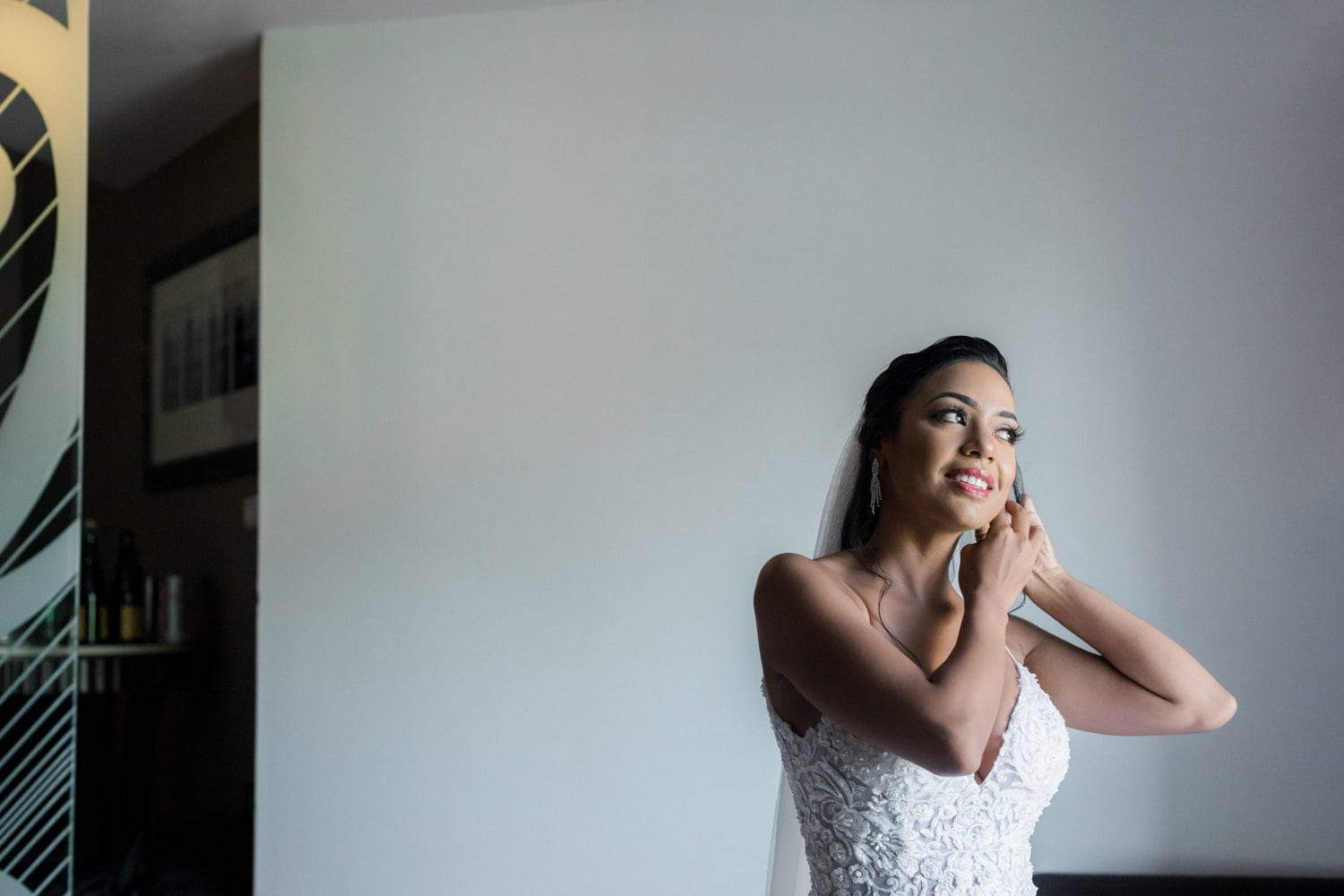 Photo of bride putting on earrings in bridal suite at Hard Rock Resort, Dominican Republic.