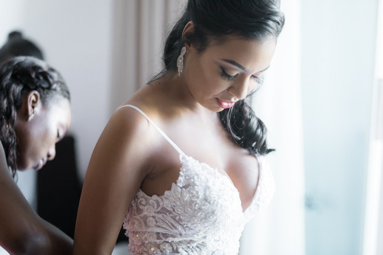 Bridesmaid helping gorgeous bride put on wedding dress in bridal suite.