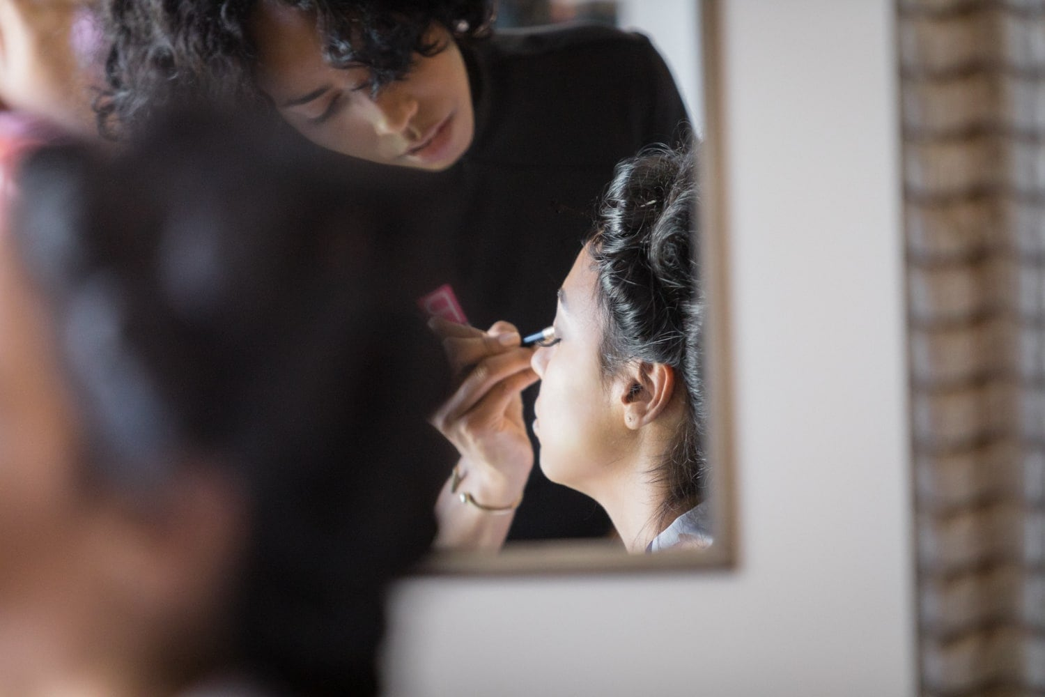 Stylist putting on bride's makeup in suite at Hard Rock Resort, Punta Cana.