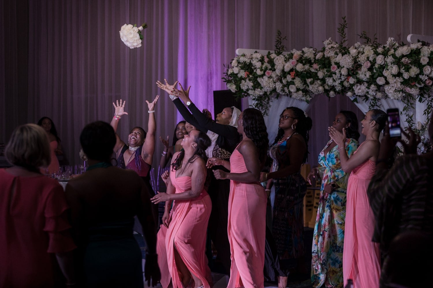 Bridesmaids jostling for position to catch the bridal bouquet.