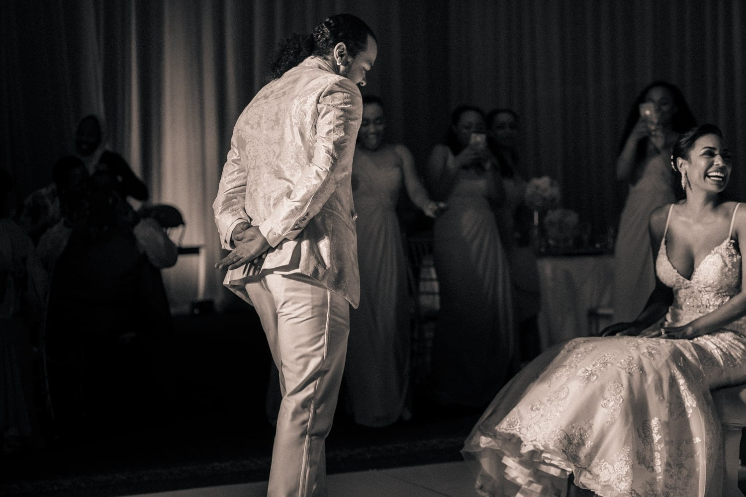 Groom's about to remove his bride's garter at wedding reception at Hard Rock in Punta Cana.
