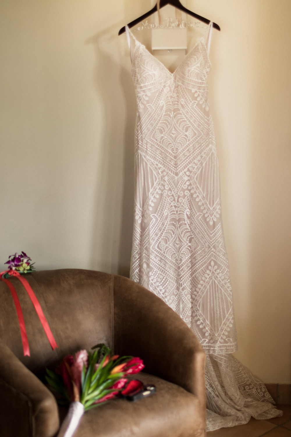 Photo of wedding dress hanging on wall in bridal suite.