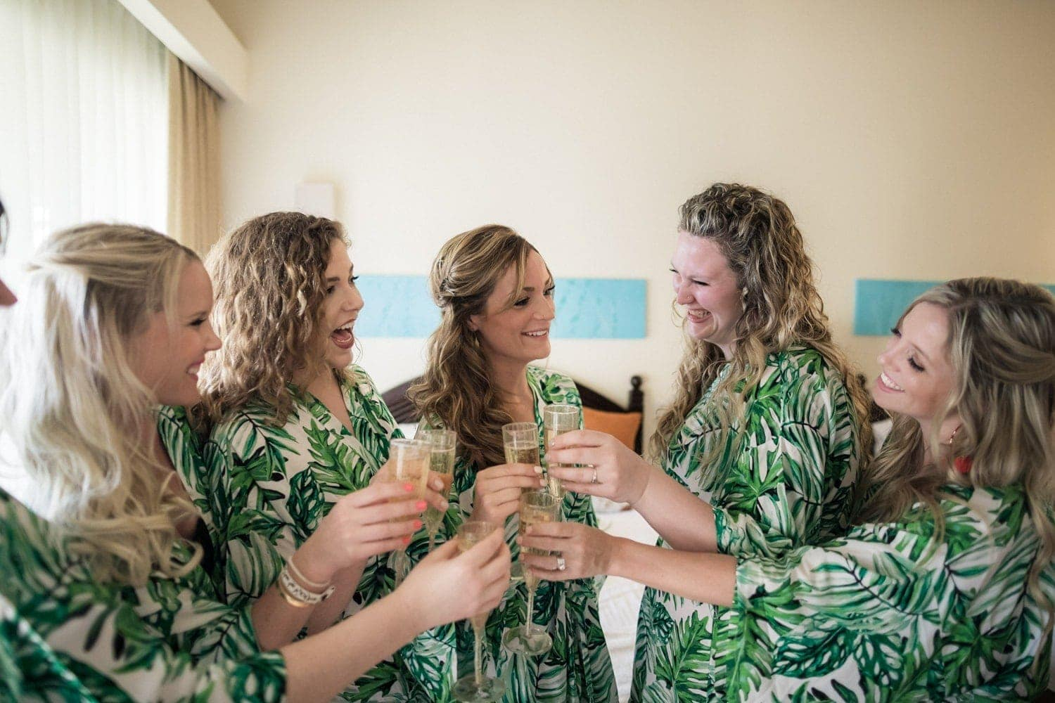 Bridesmaids and brides wearing wedding day robes while preparing for ceremony.