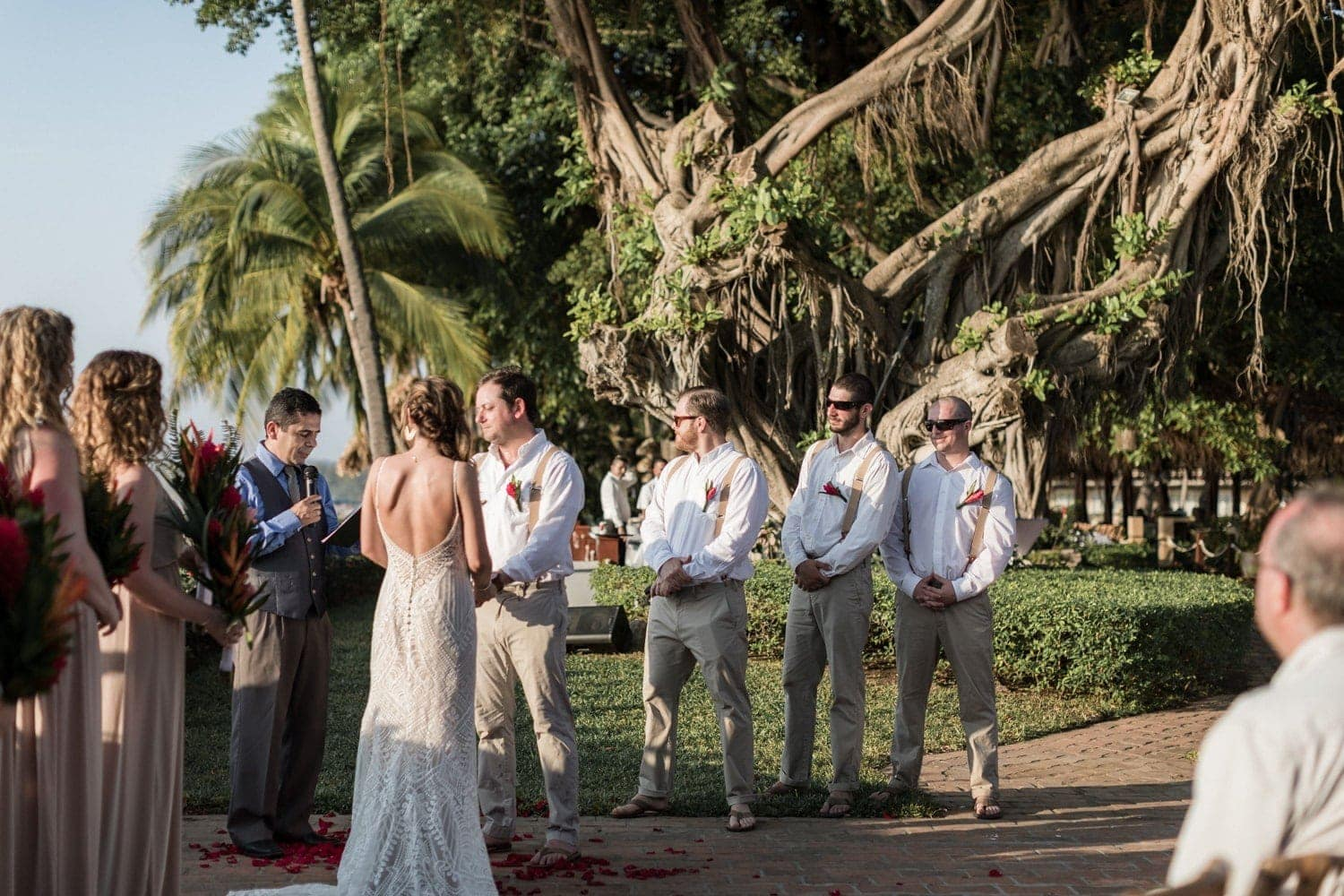 Great photo of couple getting married with bridesmaids and groomsmen on each side.