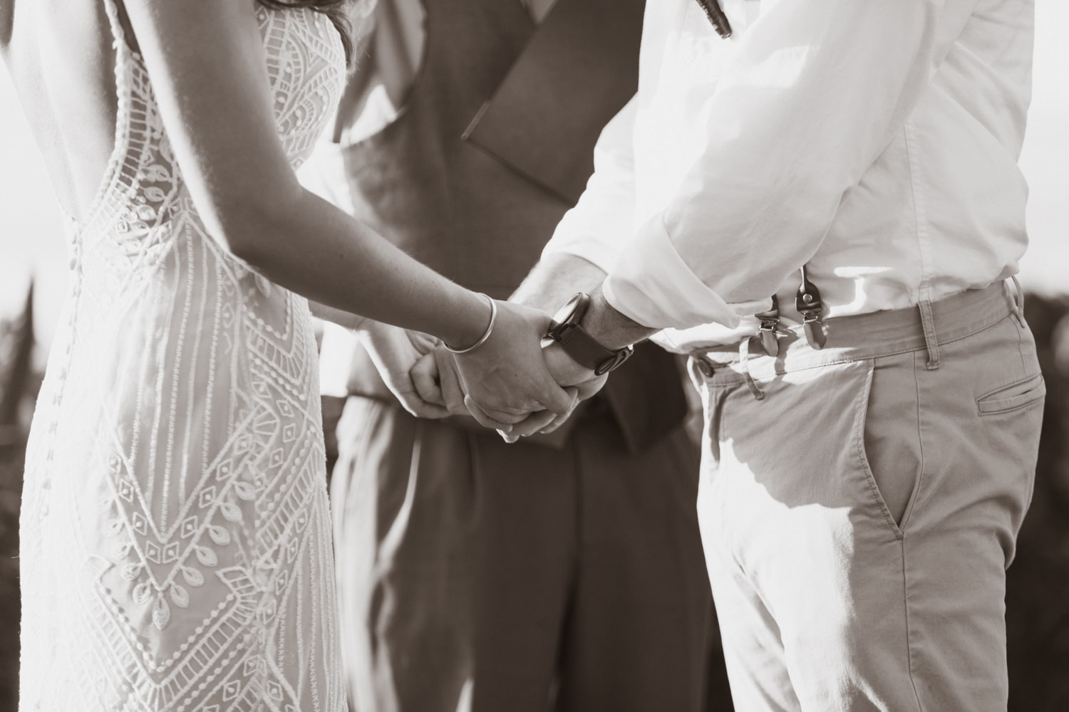 Black and white photo of couple holding hands while saying their wedding vows.