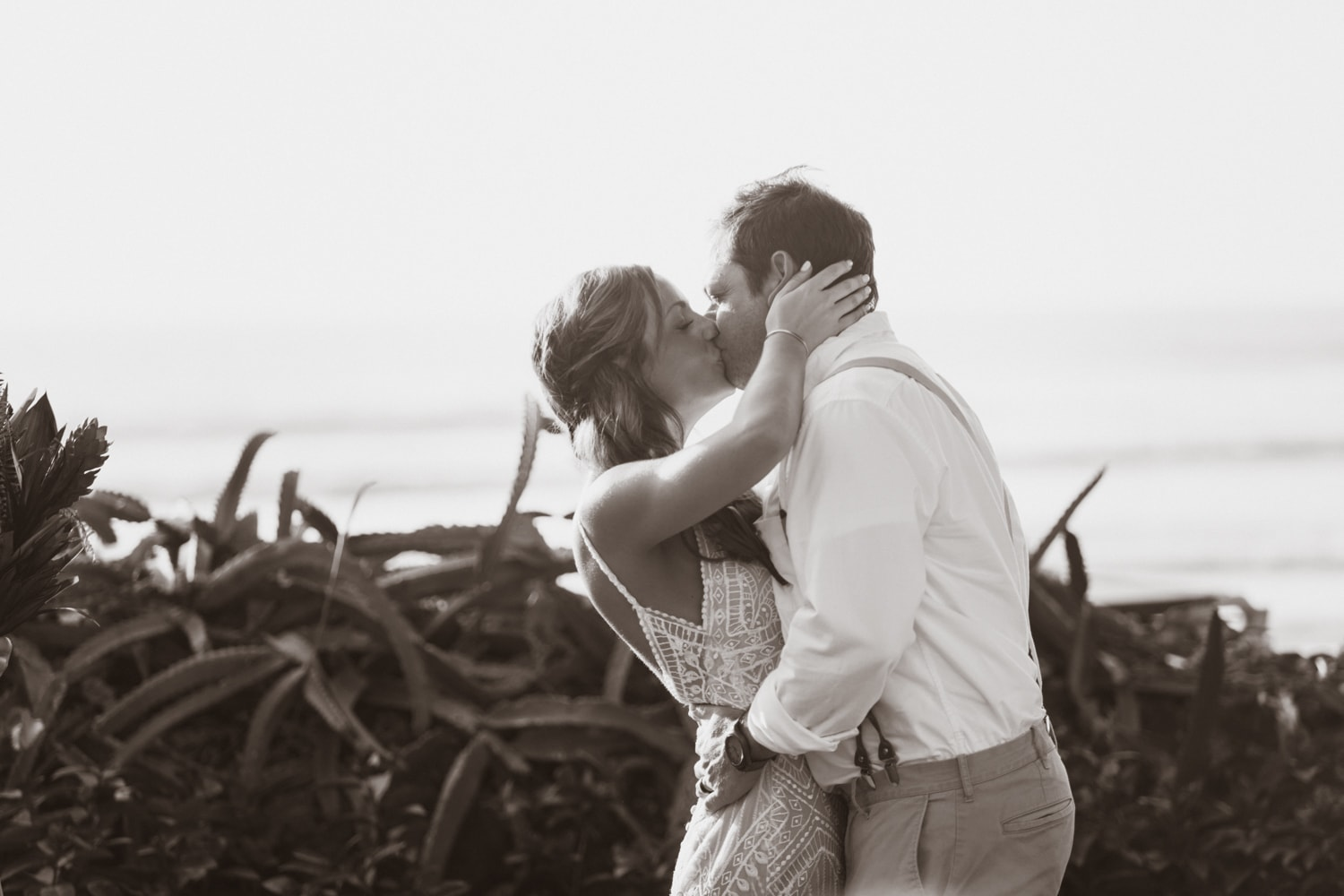 Black and white photo of newlyweds kissing after saying I do.