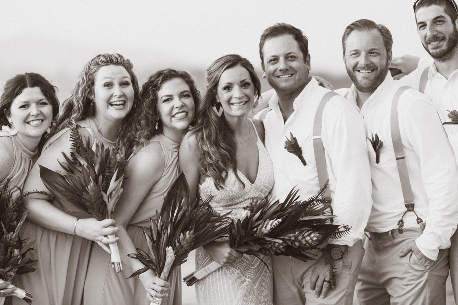 Black and white photo of just-married couple on beach surrounded by bridesmaids and groomsmen.