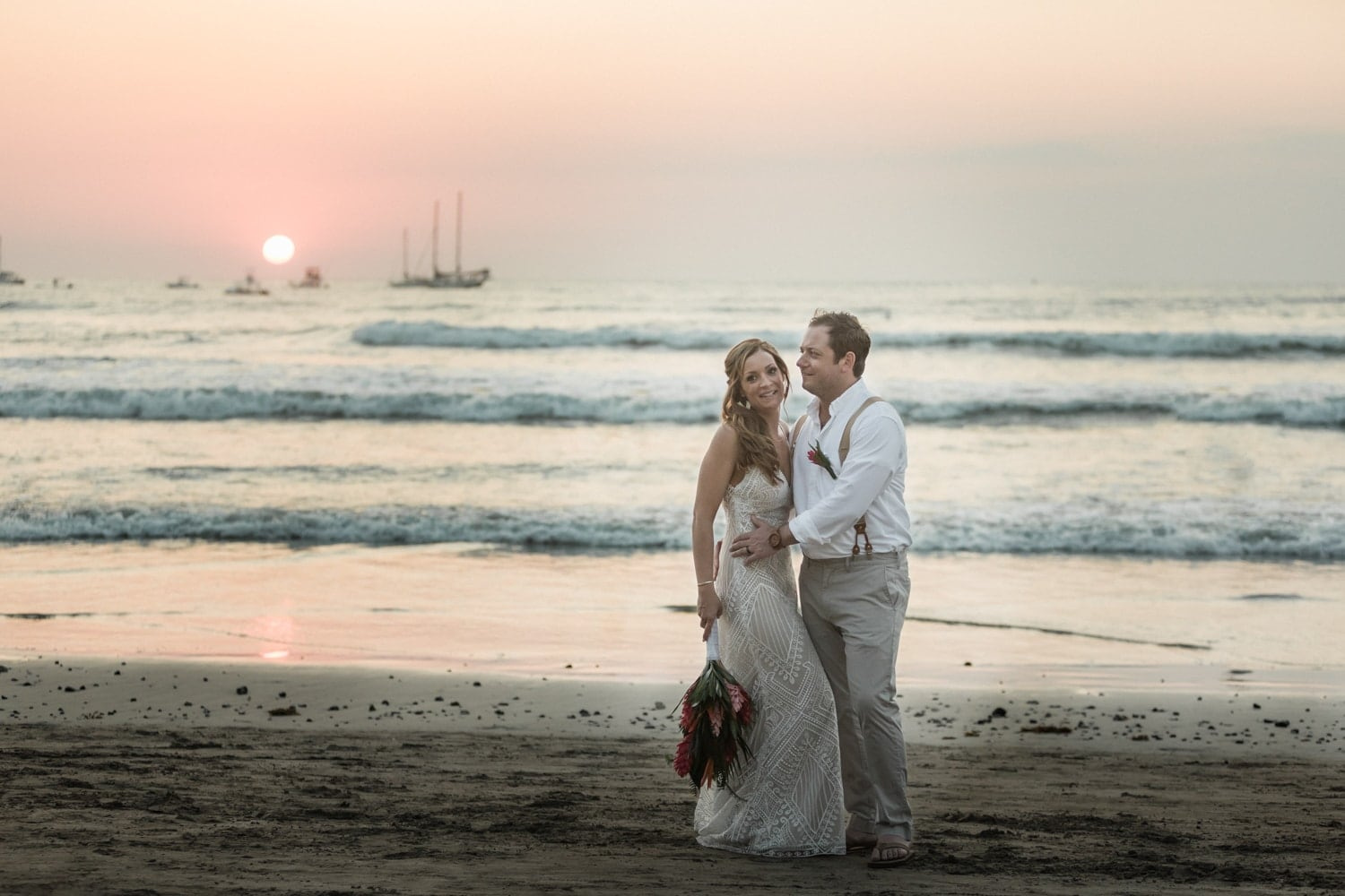Wedding photo of just-married couple on Tamarindo Beach in Costa Ria at sunset.