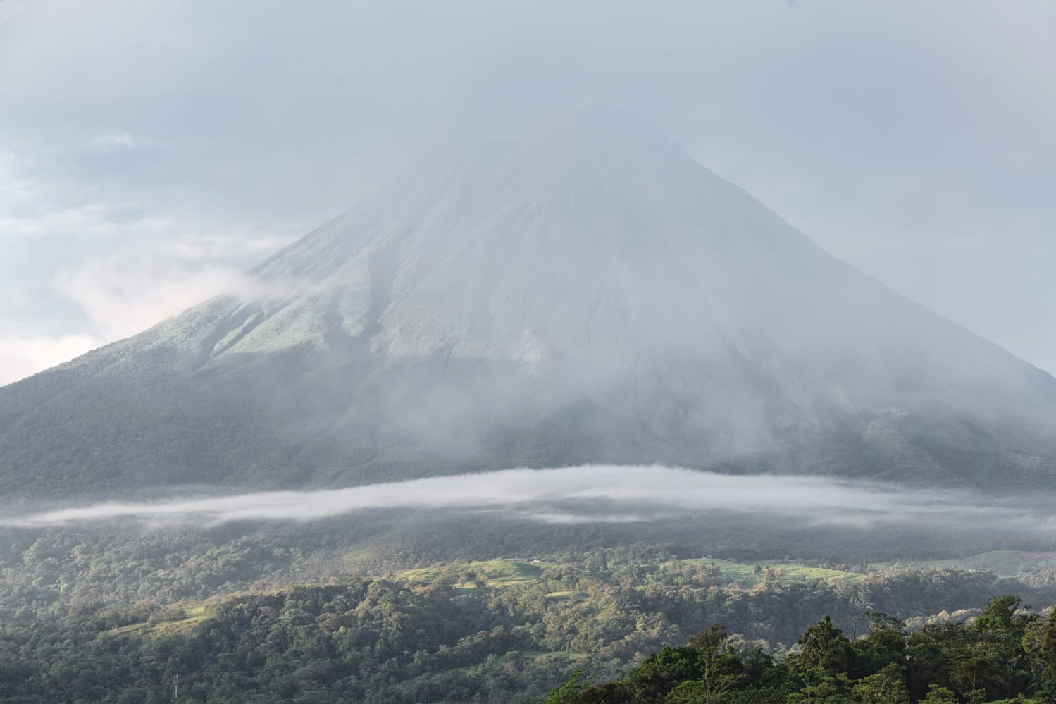 A view of the Arenal Volcano in La Fortuna enveloped in haze as seen from a guest suite at The Springs Resort & Spa.