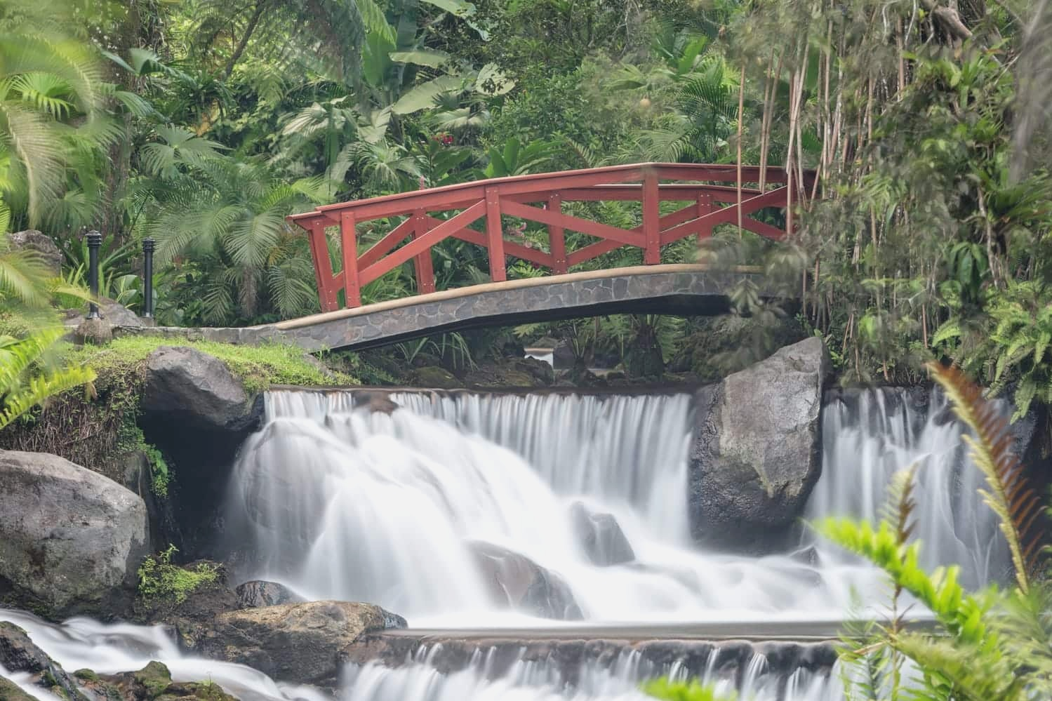This picturesque red bridge crossing a waterfall feed by a volcanic thermal spring is located at Tabacón Thermal Resort and Spa in La Fortuna, a great wedding venue in Costa Rica.