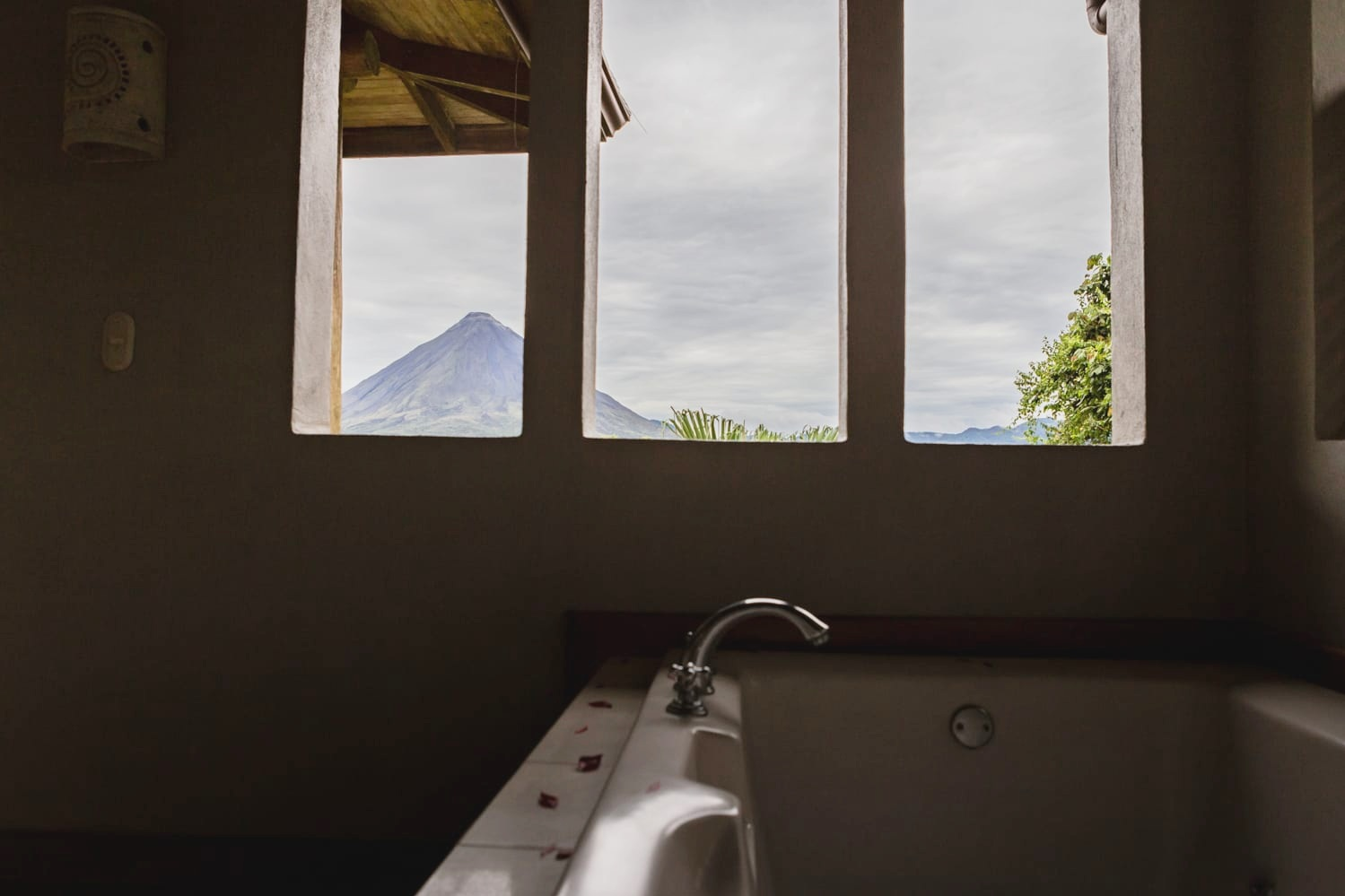 An amazing view of the Arenal Volcano in La Fortuna from a tub in a honeymoon suite decorate with red rose petals.