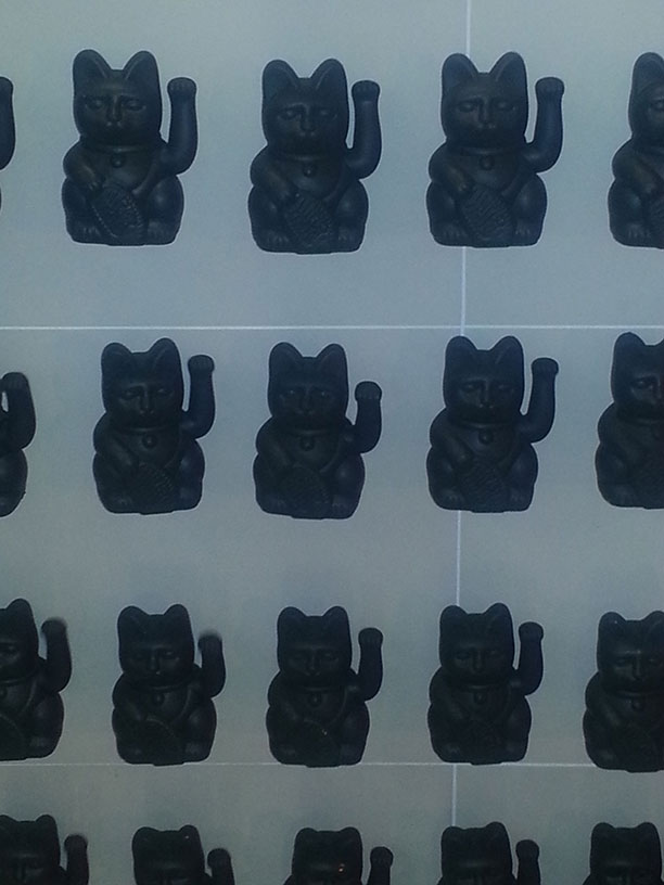ENDLESS GAIN: 400+ black maneki-nekos (or waving lucky cats)