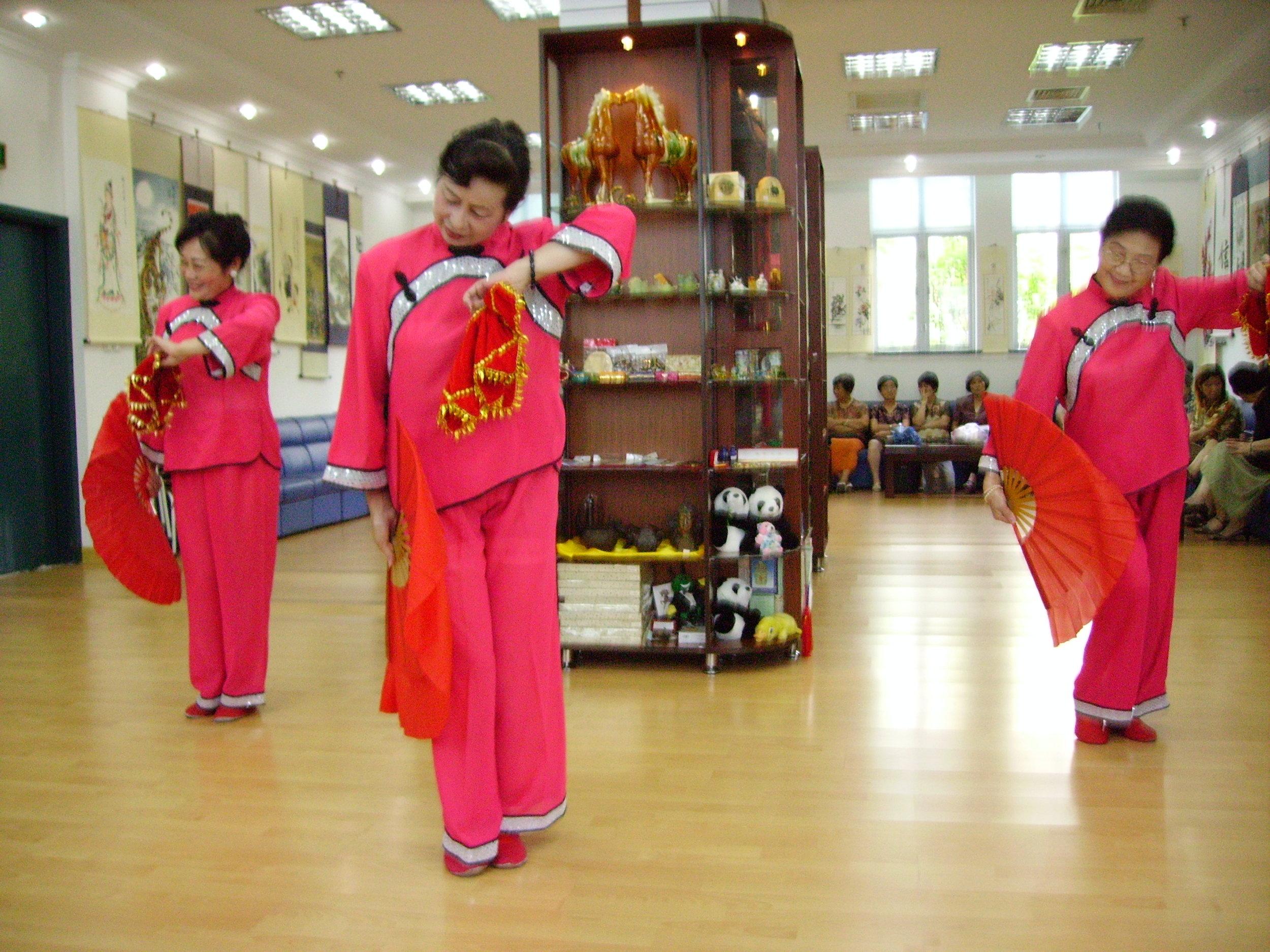 Women dancing in the culture centre, China, Clark Zlotchew, 2005