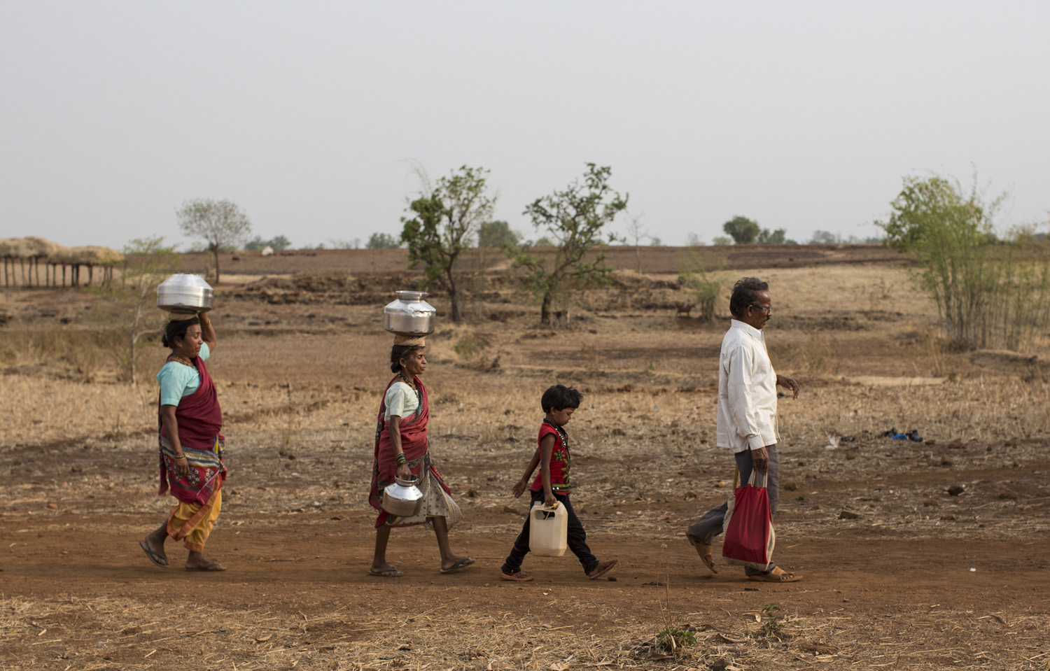 Bhaagi and Sakhri, wives of Sakharam Bhagat walk to fetch water from a well outside Denganmal village.