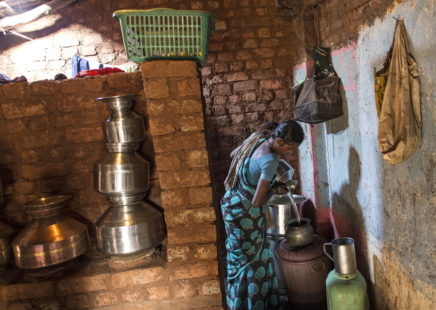 Shivarti, second wife of Namdeo, empties a water pitcher as she gets ready to fill water from a well outside Denganmal village.