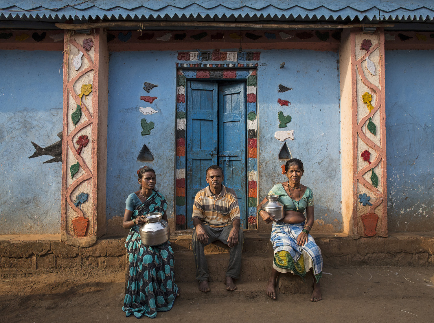Namdeo poses with his wives Shivarti (L) and Bagabai (R) outside their house in Denganmal village.